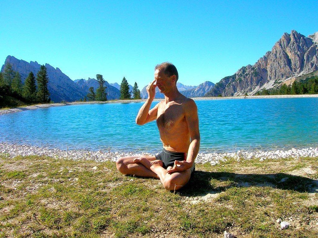 Practicing pranayama breathwork by a lake